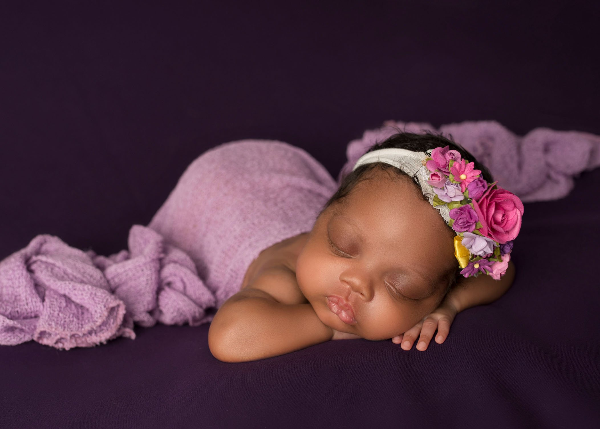African american newborn baby girl sleeping with her head on her hands draped in lavender