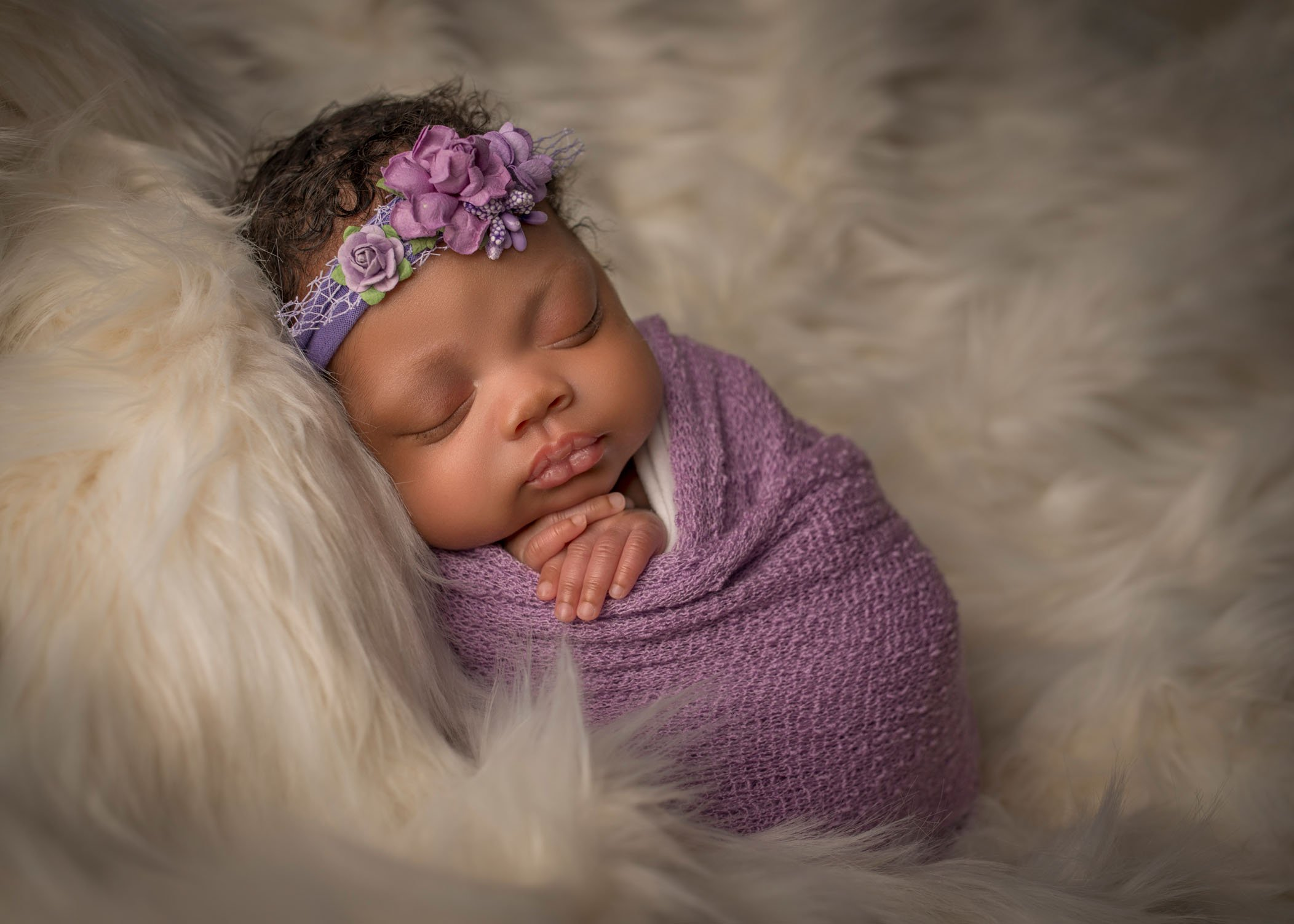 African american newborn baby girl wrapped in lavender blanket with floral headband