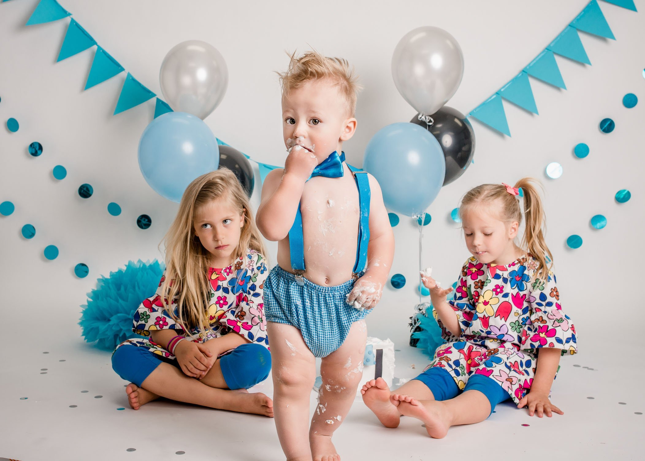 12 month old boy and his sisters at his cake smash session